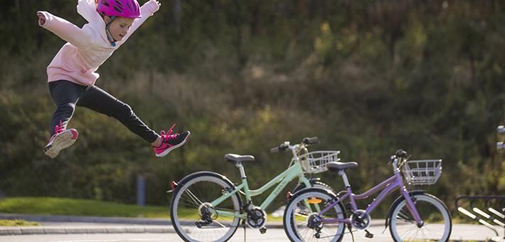 Bilde av et barn med sykkelhjelm som hopper av glede med to DBS barnesykler i bakgrunnen.