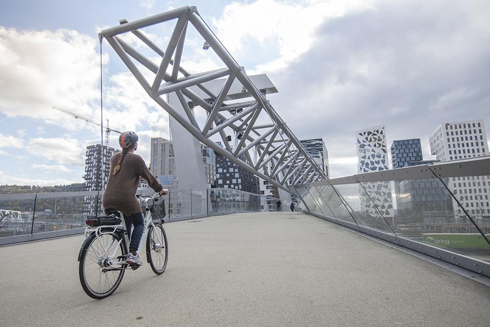 """Bilde av en kvinnelig DBS-syklist som sykler over gangbroen """"Akrobaten"""" ved Oslo sentralstasjon."""
